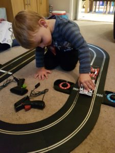 Joshua placing cars on the finish line of the Scalextric Le Mans Sports Cars track